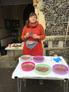 The artist, Caitlin, standing outside Laxfield Church, behind a table set out with clay moulds