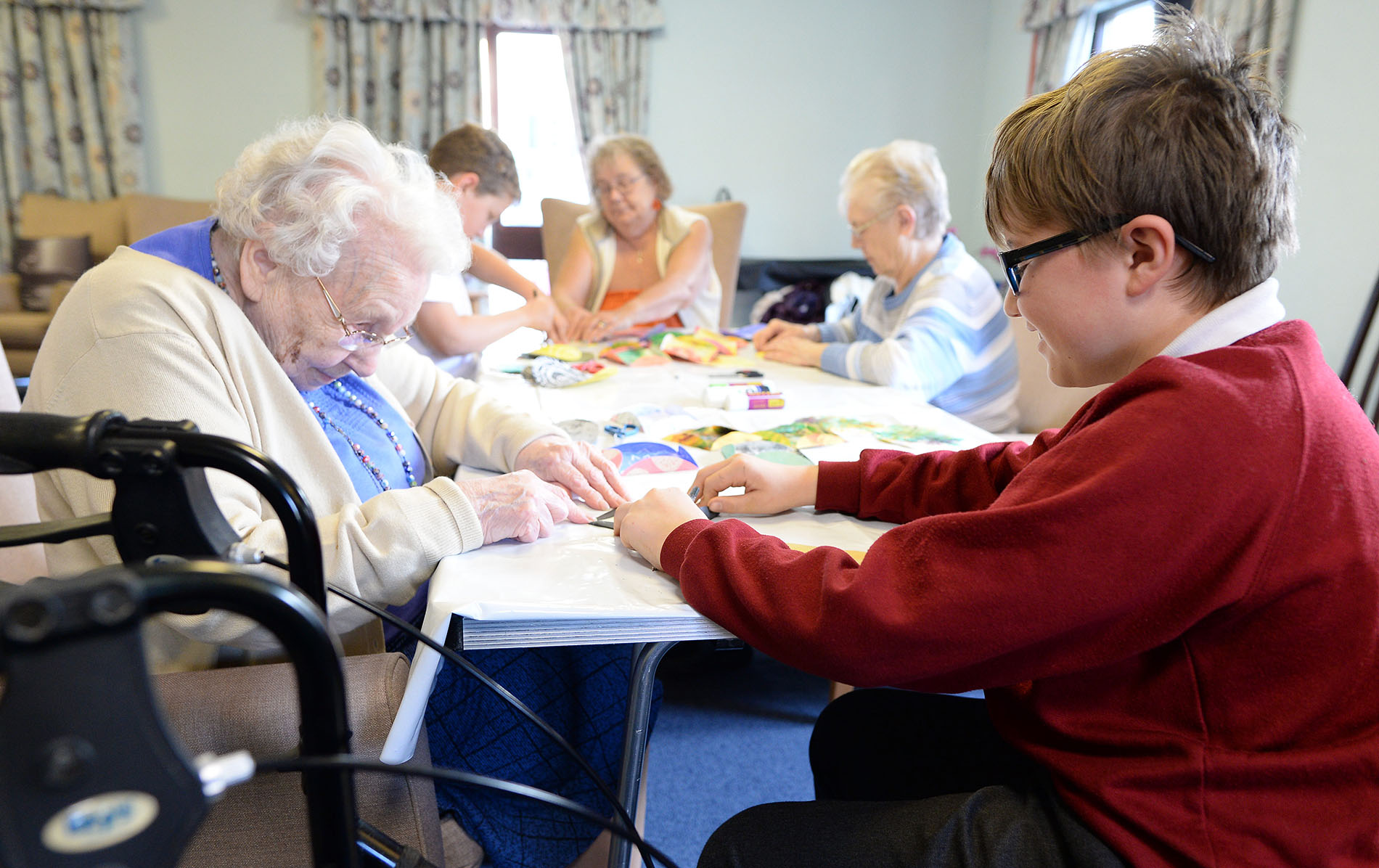 Primary school pupil during a creative session with a care home resident